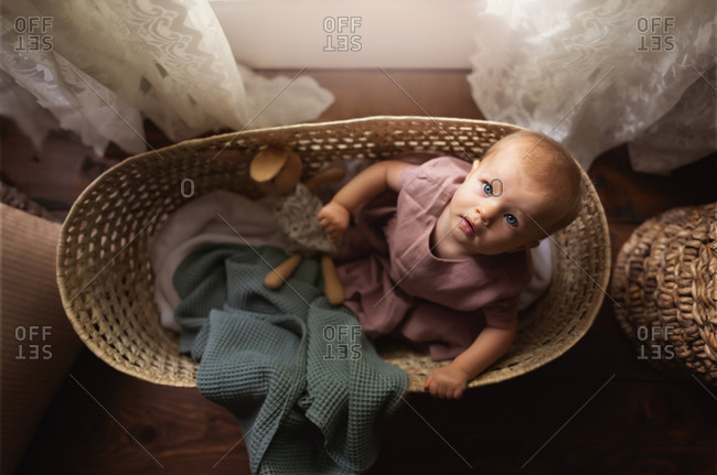 Overhead shot of little girl sitting in wicker basket with toys