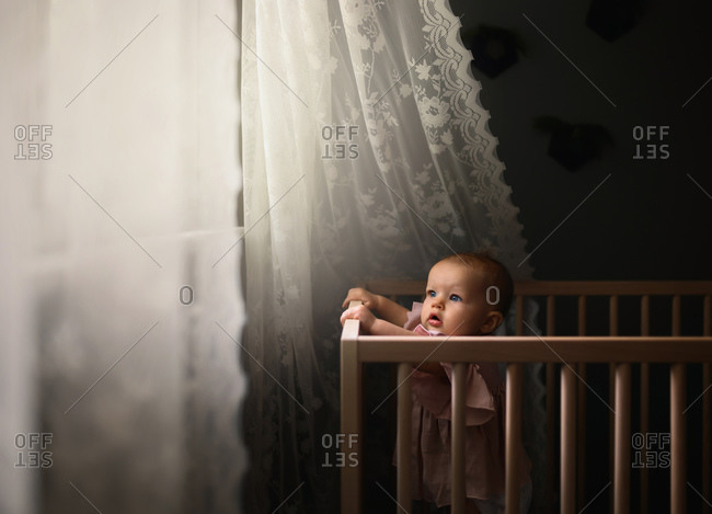 Little girl in crib, looking out window