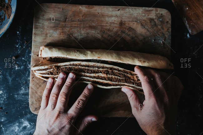 View from above of a man working cinnamon babka dough with his hands on a wooden cutting board on a black floured countertop