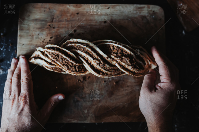 View from above of a man finishing shaping a cinnamon babka with his hands on a wooden cutting board on a black floured countertop