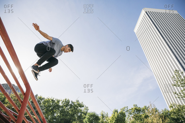 Young man performing parkour over railing against clear sky in city