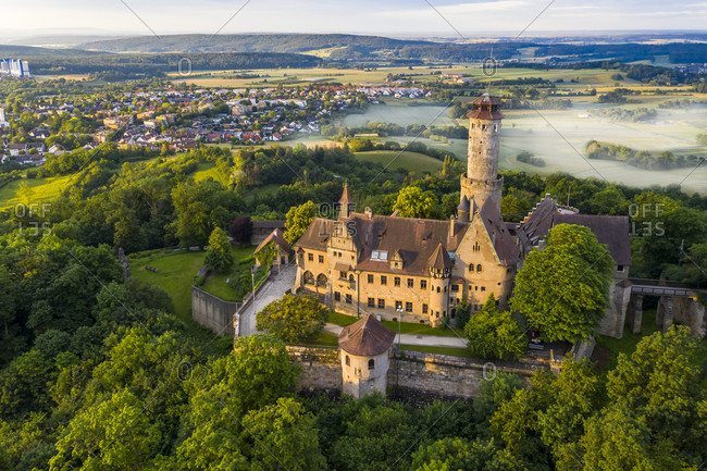 Germany- Bavaria- Bamberg- Helicopter view of Altenburg castle at foggy summer dawn