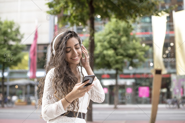 Smiling young woman listening music and using smart phone while standing in city