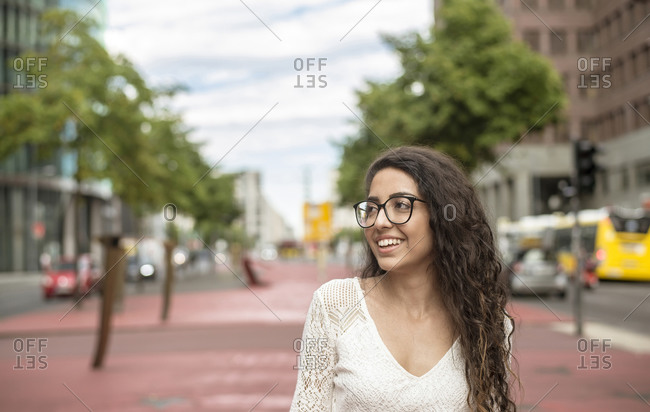 Smiling young woman wearing eyeglasses looking away while standing on footpath in city