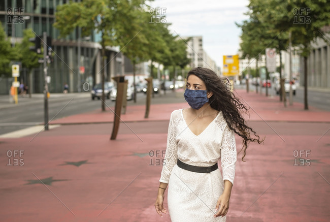 Young woman wearing mask looking away while walking on footpath in city