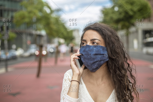 Close-up of young woman wearing mask talking over mobile phone in city