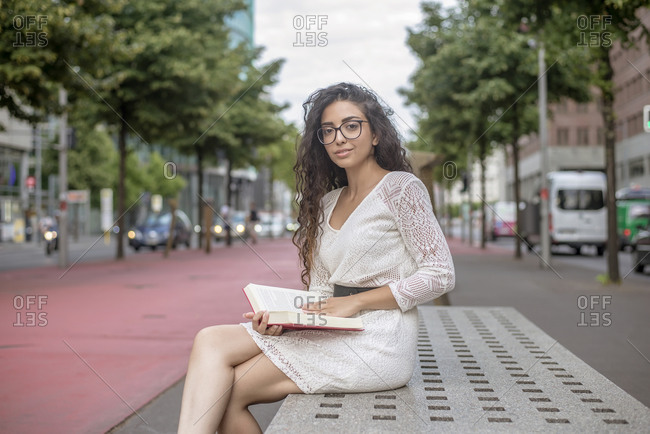 Young woman with long hair reading book while sitting on seat in city