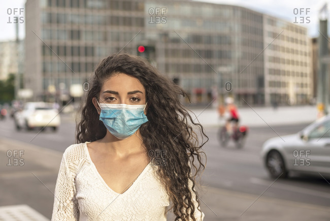 Young woman with wavy hair wearing mask while standing on street in city