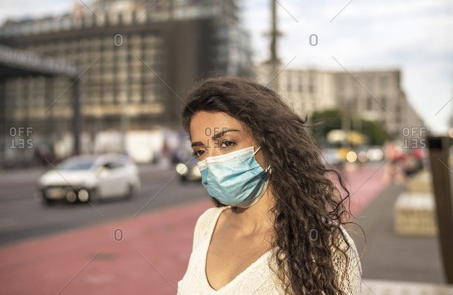 Young woman wearing mask looking away while standing on footpath in city