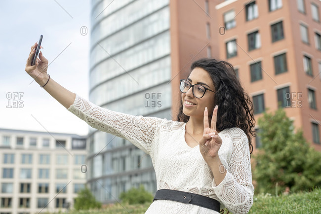Smiling young woman showing peace sign while taking selfie with smart phone in city