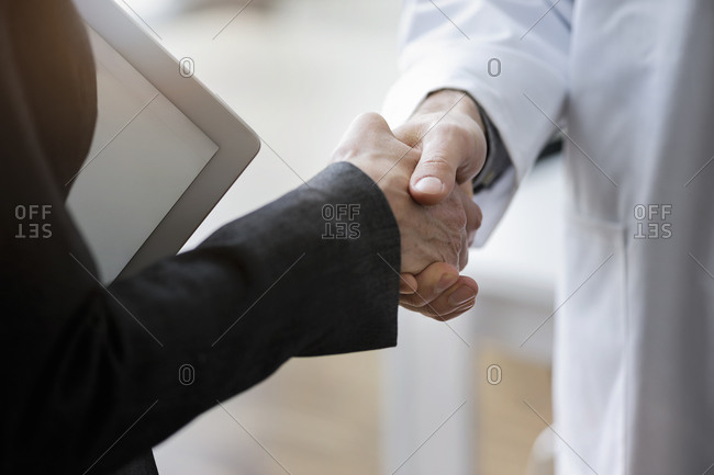 Close-up of male and female partners giving handshake in office