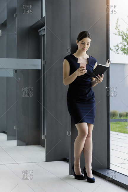 Businesswoman holding diary using smart phone while standing against wall in office