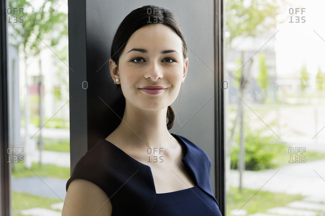 Close-up of smiling businesswoman by window in office