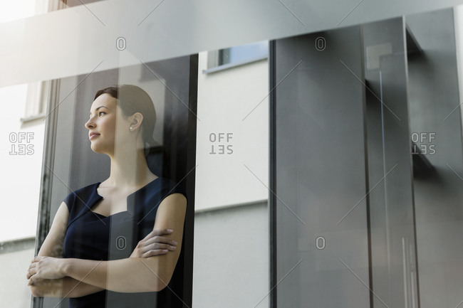 Thoughtful female entrepreneur with arms crossed standing in office seen through glass door