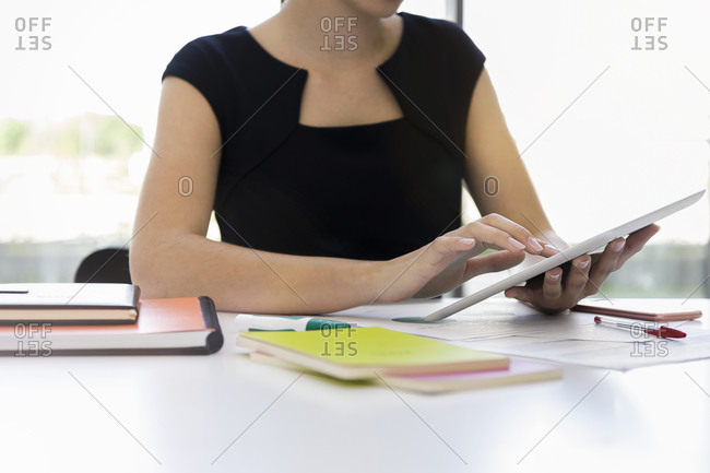Close-up of businesswoman using digital tablet at desk in office