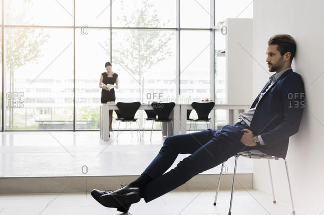 Thoughtful businessman sitting on chair while female colleague working in background at office
