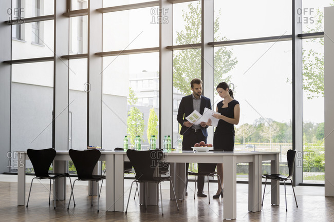 Colleagues discussing reports while standing at desk against window in office
