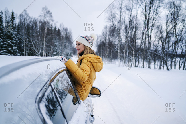 Smiling mature woman sitting on car window against snow covered landscape