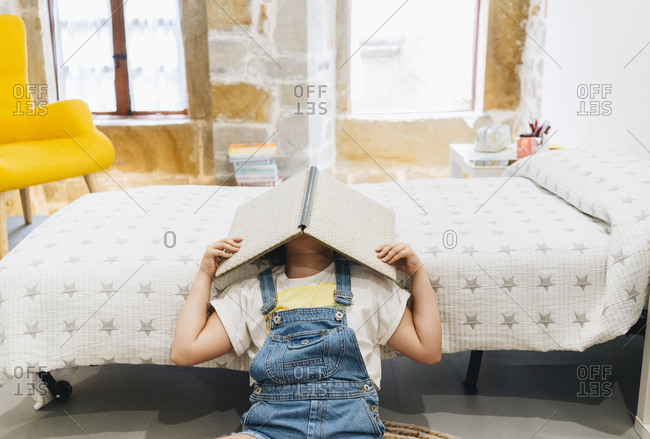 Little girl covering face with book while sitting at home in bedroom