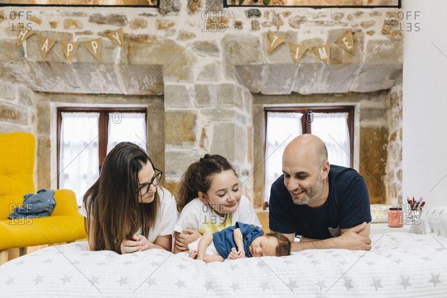 Parents and sister looking at new born baby while lying on bed at home