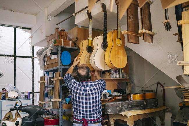 Senior man hanging guitar in a line at workshop