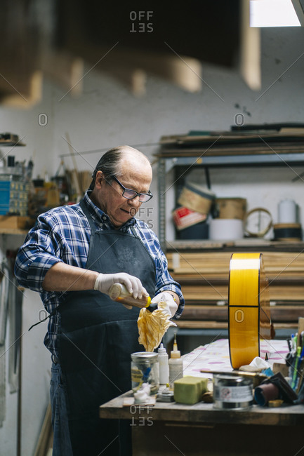 Luthier polishing guitar while standing by workbench at workshop