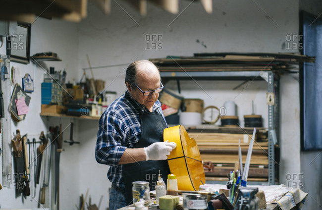Man polishing guitar while standing by workbench at workshop