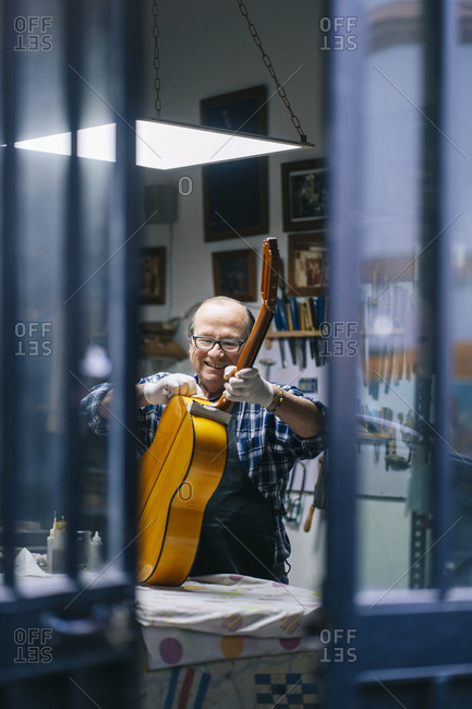 Smiling man cleaning guitar while working at workshop
