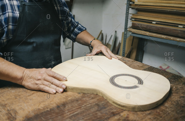 Craftsman making guitar while standing by workbench at workshop
