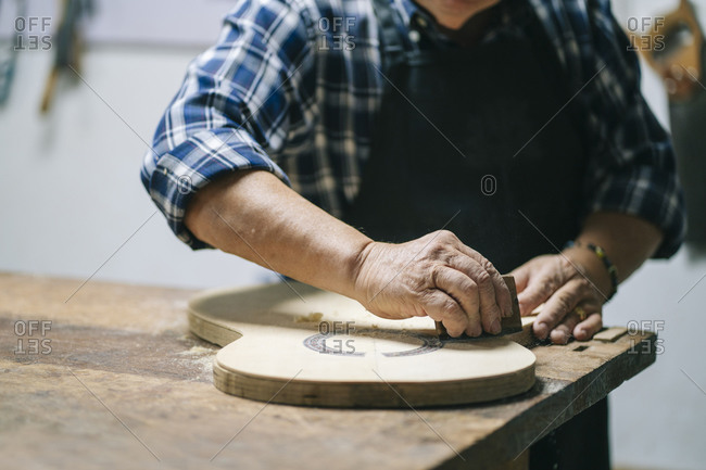 Man molding shape of guitar while standing at workshop