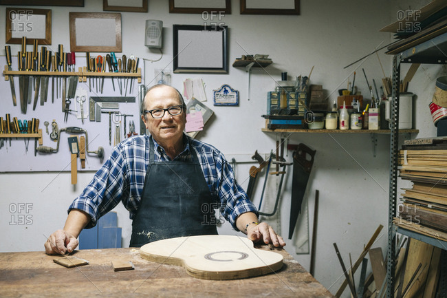 Smiling man standing by workbench at workshop