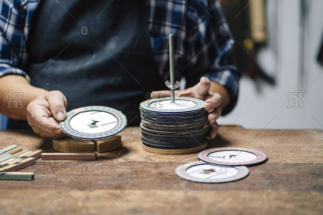 Luthier selecting paper disk while standing at workshop