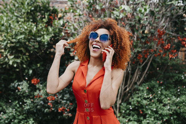 Cheerful afro young woman talking over smart phone while standing against plants in park