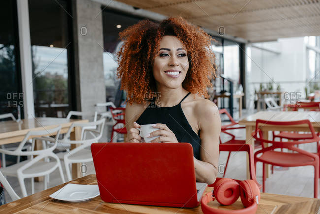 Smiling afro woman with laptop on table holding coffee cup while sitting at sidewalk cafe