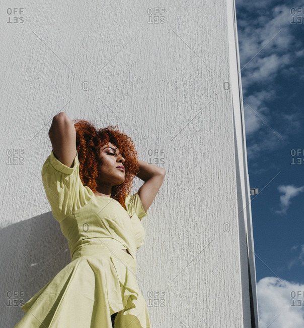 Young woman with hands in hair standing by white wall during sunny day