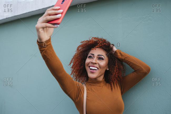Cheerful afro young woman taking selfie with smart phone while standing by wall