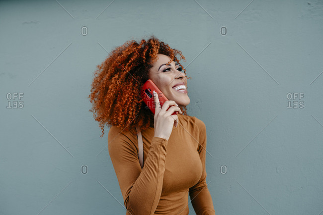 Cheerful young woman with afro hair talking over mobile phone while standing against wall