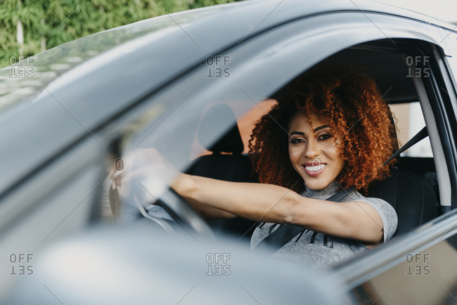 Smiling young woman with afro hair driving car seen through window