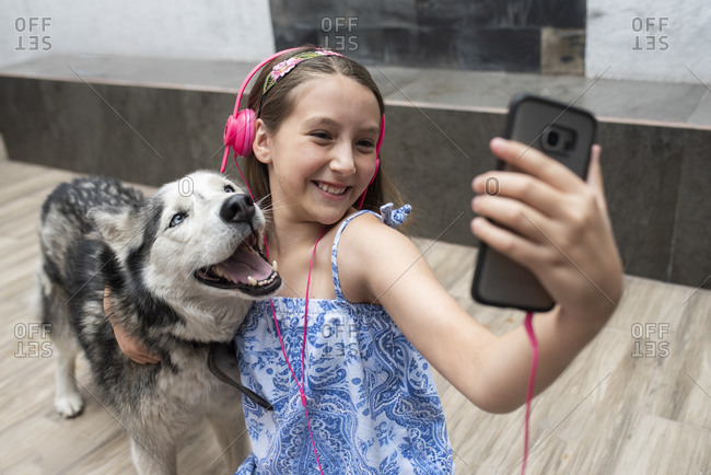 Smiling girl taking selfie with dog while sitting on floor at home