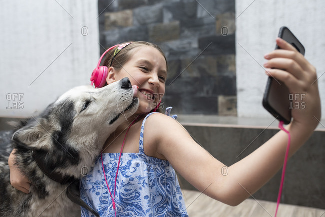 Girl taking selfie with dog through mobile phone at home