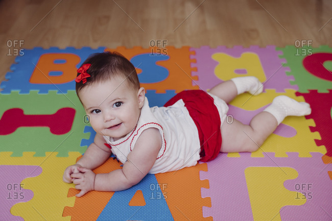 Cute smiling baby girl lying on colorful puzzle playmat at home