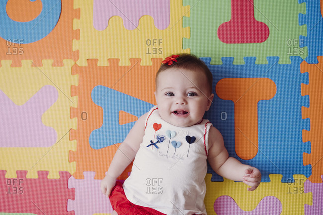 Cute baby girl relaxing on colorful alphabetical puzzle playmat at home