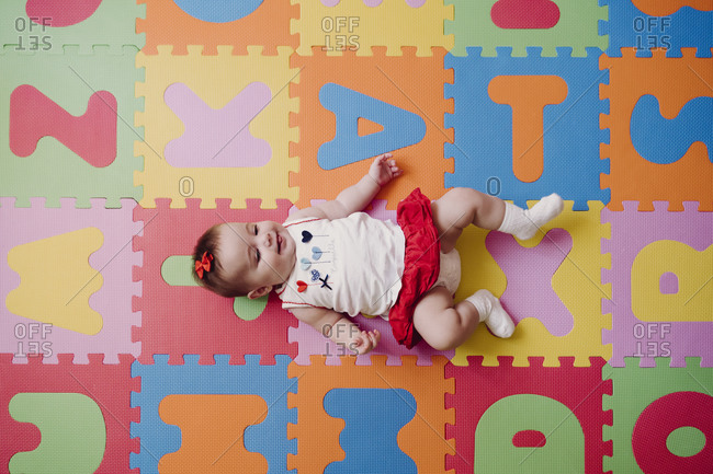 Cute baby girl lying on colorful alphabetical puzzle playmat at home