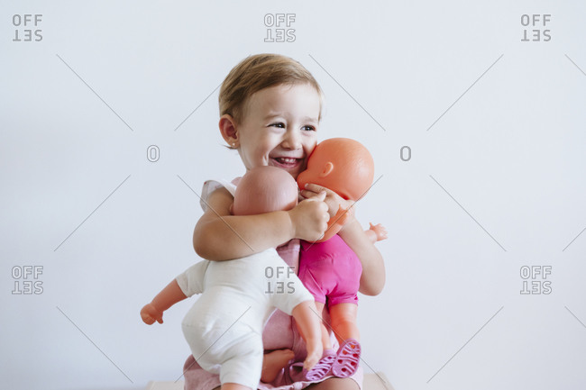 Baby girl embracing toys while sitting against wall