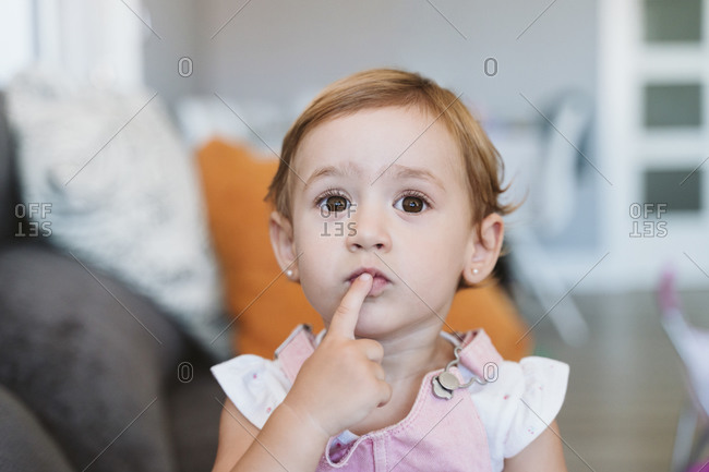 Thoughtful baby girl with finger on lips sitting on sofa at home