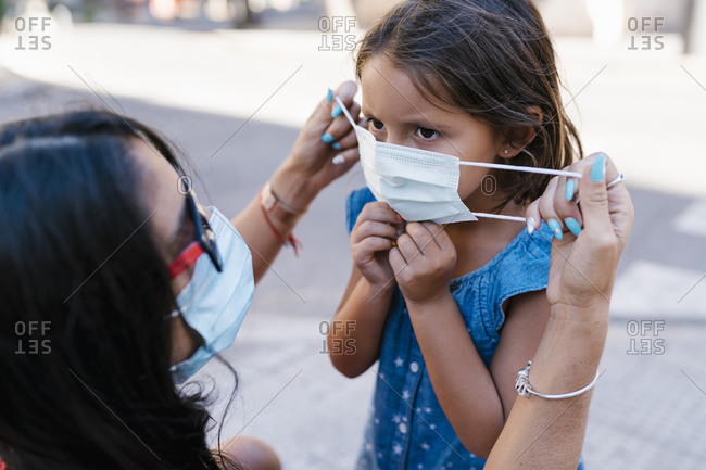 Close-up of mother wearing face mask to daughter on street