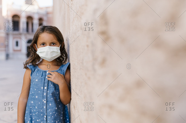Girl wearing mask standing by wall in city