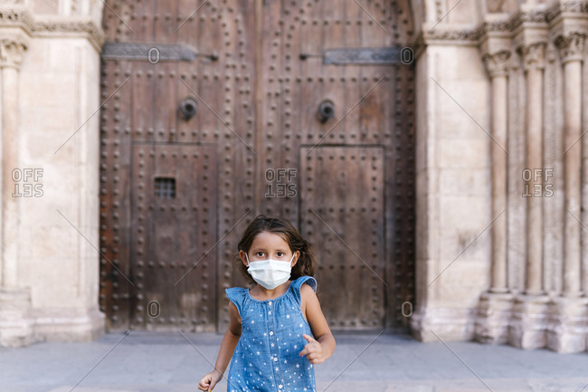 Girl wearing mask running in front of historic door
