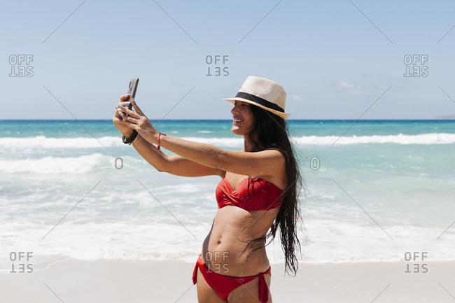 Woman wearing bikini taking selfie with smart phone while standing against sea