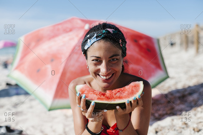 Close-up of smiling woman holding watermelon while sitting against red umbrella at beach